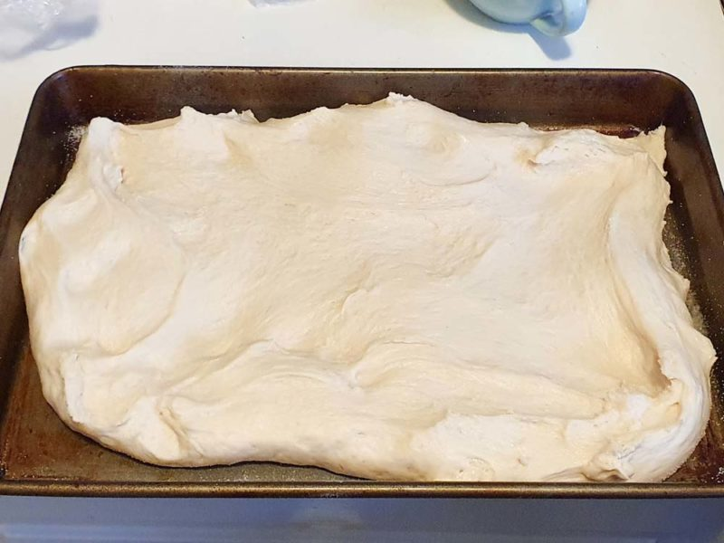 presssing out focaccia onto a tray