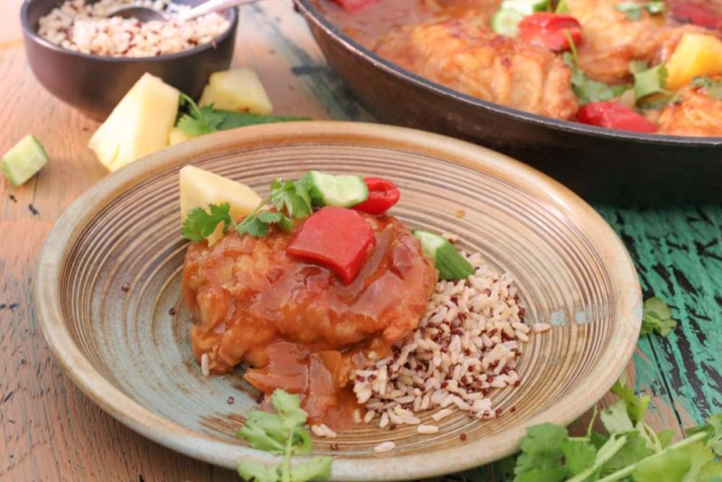 A plate with roasted chicken in sweet and sour sauce